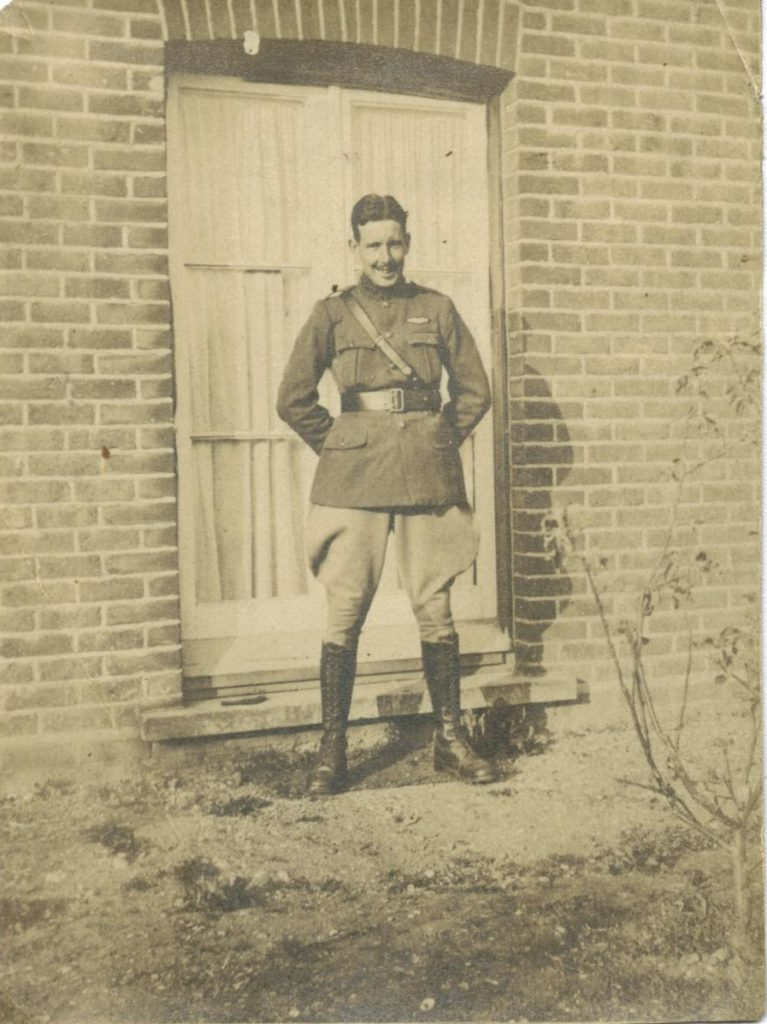 Photo of a smiling Curtis in uniform with his pilots wings above his left breast pocket; he is standing before a tall window outside a brick house.