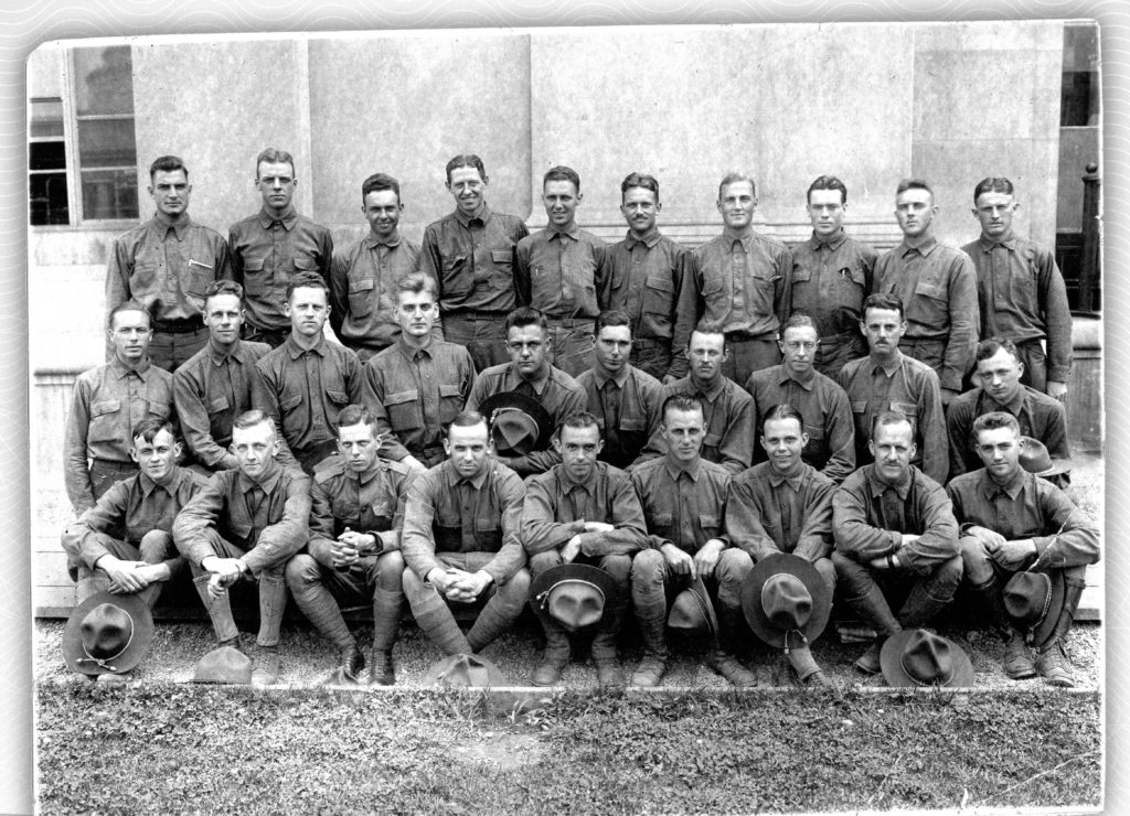 Photo of nineteen men in three rows, all dressed similarly in long sleeved Oxford shirts without ties. Many of the men seated in the front row are holding campaign hats, but all are bare-headed.