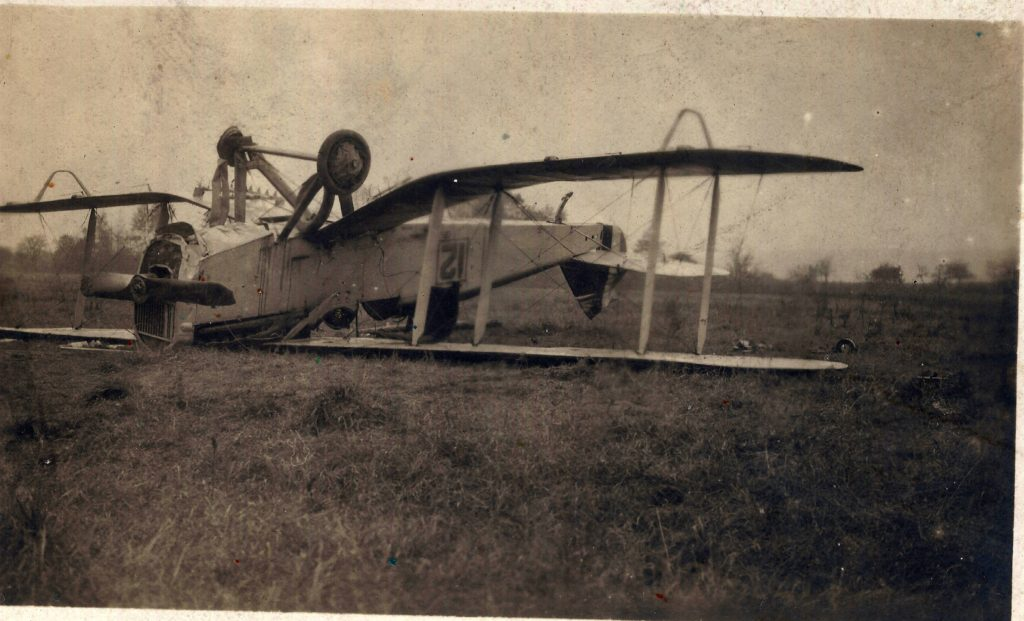 A biplane on its back in a field.