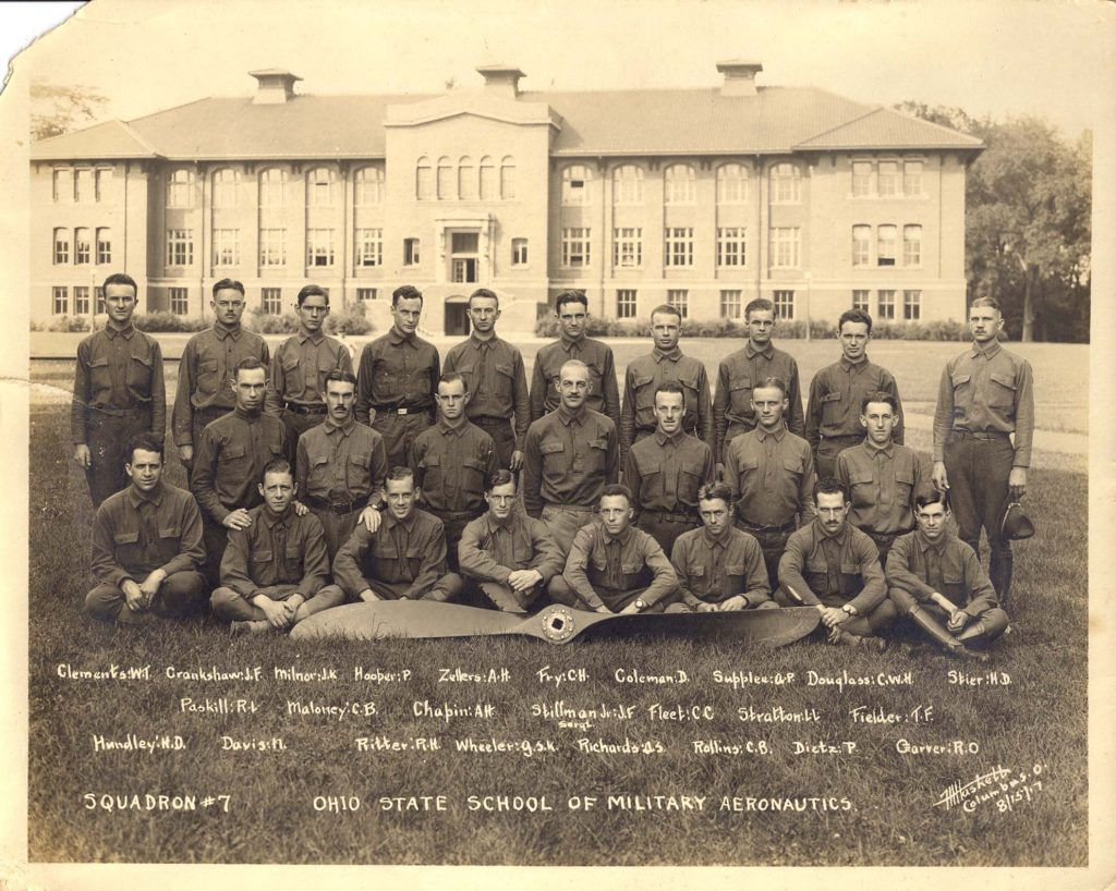 """Photo of 25 men seated and standing on grass before a large academic building with an airplane propeller in front of them, with their names handwritten in and the legend """"Squadron # 7 Ohio State School of Military Aeronautics."""""""