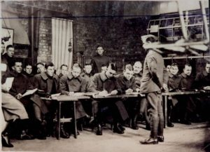 Photo of men in heavy coats, mostly seated at a table, apparently listening and taking notes from an instructor standing in front of them.