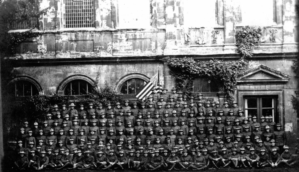 Large group photo of about 180 men in uniform ranged in about 10 rows before an American flag and ivy-covered walls.