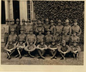Photo of 28 men in uniform wearing campaign hats, arranged in three rows, the men in front sitting, the two rows behind standing.